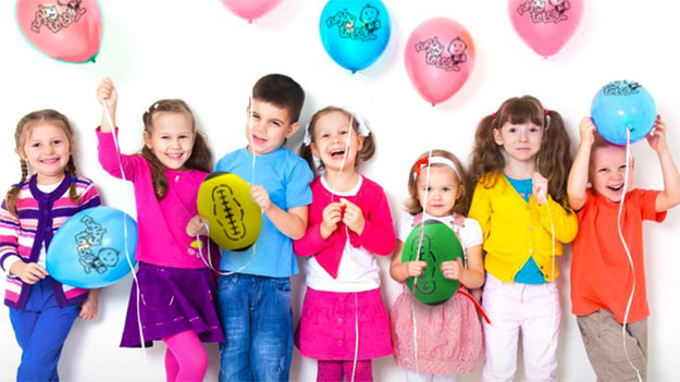 Group of smiling children holding party balloons and rugby balls for kids rugby party